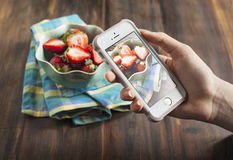 Smartphone shot food photo. Hands taking photo of fresh strawberry Stock Photo