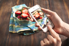 Smartphone shot food photo. Hands taking photo of fresh strawberry on smart phone royalty free stock images