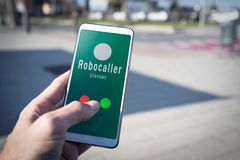 Smartphone showing a call from a robocaller on screen. Smartphone showing on screen an illegal robocall. Smartphone showing a call from a robocaller on screen stock photography