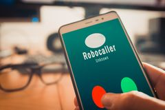 Smartphone showing a call from a robocaller on screen. Smartphone showing on screen an illegal robocall. Smartphone showing a call from a robocaller on screen stock images
