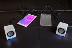 Smartphone with silicone case and portable speakers stock photo