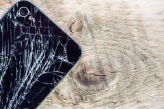 Smartphone skärm med brutet exponeringsglas på en woddentabell Royaltyfri Foto