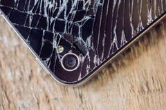 Smartphone skärm med brutet exponeringsglas på en woddentabell Arkivbilder
