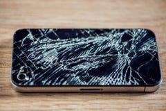 Smartphone skärm med brutet exponeringsglas på en woddentabell Royaltyfri Bild