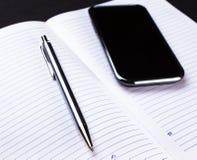 Smartphone skrivar och anteckningsboken på svart Arkivbild