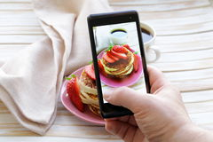 Smartphone sköt matfotoet - pannkakor för frukost med jordgubbar Royaltyfria Bilder