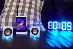 Smartphone, small speakers and LED clock stock photos