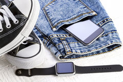 Smartphone, smartwatch, jeans and sport shoes Royalty Free Stock Photos
