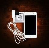 Smartphone, with socket and wire charging against a wall Stock Images