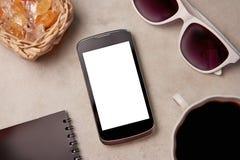 Smartphone, solglasögon, penna och kaffe på Royaltyfria Bilder