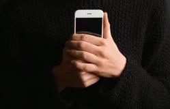 Smartphone solo de la tenencia de la mujer en fondo negro imagen de archivo libre de regalías