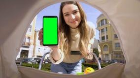 Smartphone sonriente de la pantalla del verde de la demostración de la mamá al bebé en el carro, app de la nana metrajes