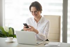 Smartphone sonriente de la tenencia de la empresaria usando el negocio móvil a fotos de archivo libres de regalías