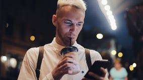 Smartphone sonriente del usingn del hombre en ciudad de la noche Hombre joven hermoso usando smartphone en la noche y el café de  almacen de metraje de vídeo