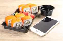 Smartphone with space for text and sushi rolls served on wooden table. Food delivery stock image
