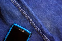 Smartphone sticks out of a pocket of blue jeans stock photography