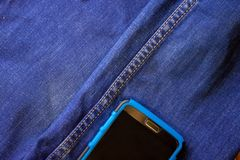 Smartphone sticks out of a pocket of blue jeans royalty free stock image