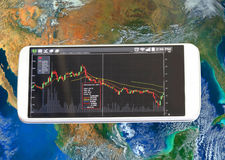 Smartphone and stock chart, investment. Smartphone and stock chart investment trading, Elements of this image furnished by NASA Royalty Free Stock Photos