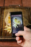 Smartphone strzelał karmową fotografię - Francuscy dłoniaki z solą fotografia stock