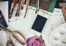 Smartphone su una tavola nello studio dell'artista Fotografie Stock
