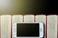 Smartphone sui precedenti dei libri Priorità bassa scura, spazio della copia Concetto: libri e aggeggi elettronici fotografia stock