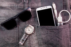 Smartphone, sunglasses, portable battery and watch on jeans back. Ground Stock Photography