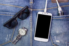 Smartphone, sunglasses, portable battery and watch on jeans back Stock Image