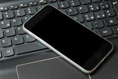Smartphone sur l'ordinateur portable Photo stock