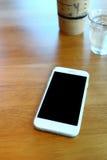 Smartphone sur le bureau en café de café Photos libres de droits