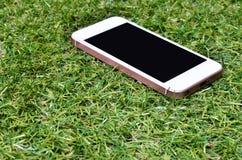 Smartphone sur le fond d'herbe Photos stock