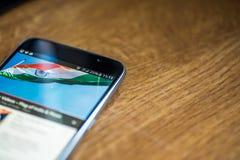 Smartphone sur le fond en bois avec le signe du réseau 5G charge de 25 pour cent et drapeau d'Inde sur l'écran Photos stock