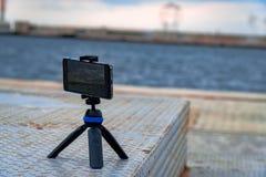 Smartphone sur un mini trépied enregistre le coucher du soleil dans le port de Salonique photos stock