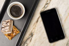 Smartphone, sweets and black coffee. On a white marble surface Royalty Free Stock Photography