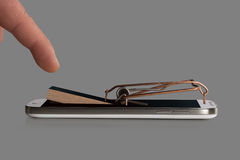 A smartphone symbolically as a mousetrap with trigger Stock Photography
