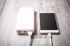 Smartphone On A Table Getting Recharged By A Powerbank, High Angle View. A Smartphone On A Table Getting Recharged By A Powerbank, High Angle View stock image