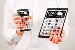 Smartphone and tablet with transparent screen in human hands. Stock Images