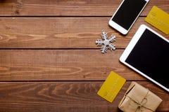 Smartphone, tableta, haciendo compras para la tabla de madera en línea del Año Nuevo Foto de archivo