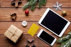 Smartphone, tableta, haciendo compras para la tabla de madera en línea del Año Nuevo Imágenes de archivo libres de regalías
