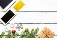 Smartphone, tableta, haciendo compras para la tabla de madera en línea del Año Nuevo Imagenes de archivo
