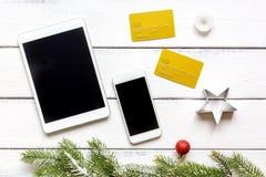 Smartphone, tableta, haciendo compras para la tabla de madera en línea del Año Nuevo Foto de archivo libre de regalías