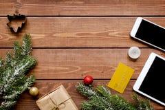Smartphone, tableta, haciendo compras para la tabla de madera en línea del Año Nuevo Imagen de archivo libre de regalías