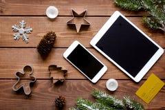Smartphone, tableta, haciendo compras para la tabla de madera en línea del Año Nuevo Fotografía de archivo