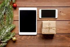 Smartphone, tableta, haciendo compras para la tabla de madera en línea del Año Nuevo Fotos de archivo libres de regalías