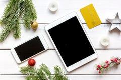 Smartphone, tableta, haciendo compras para la tabla de madera en línea del Año Nuevo Imagen de archivo