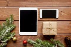 Smartphone, tableta, haciendo compras para la tabla de madera en línea del Año Nuevo Fotos de archivo