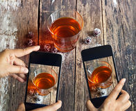 Smartphone take photos of tea and grape on wooden background, vibrant concept Royalty Free Stock Image