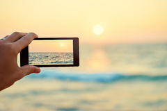 Smartphone taking picture of sea sunset Stock Photo