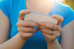 Smartphone texting. Hands of a woman in a blue t-shirt using a smart phone on a sunny day royalty free stock photo