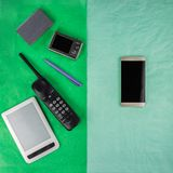 A smartphone and the things that it replaces, on different halves of a two-colored rectangle. Pale green and aquamarine rectangle stock photos