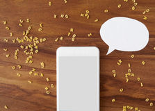 Smartphone, thought bubble, voice command, alphabet noodles, coo. King app on wooden background stock photos
